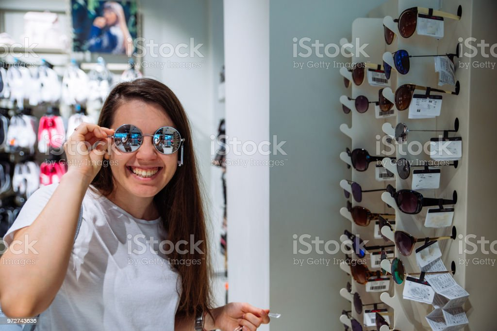 woman choosing sunglasses in mall. shopping concept stock photo