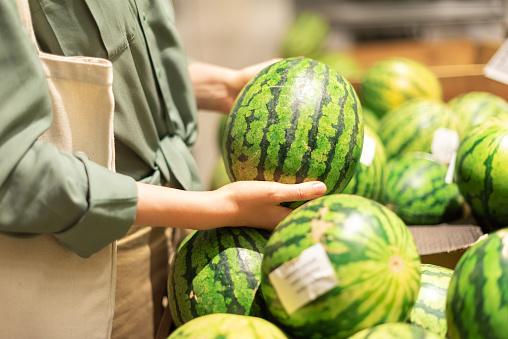 Woman choosing watermelon in market. Zero waste, plastic free concept. Sustainable lifestyle. Healthy food, bio, vegetarian diet concept