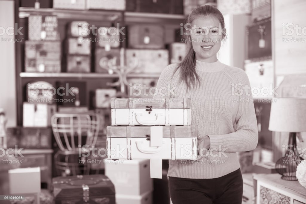 Woman choosing wooden suitcase in the furniture store royalty-free stock photo
