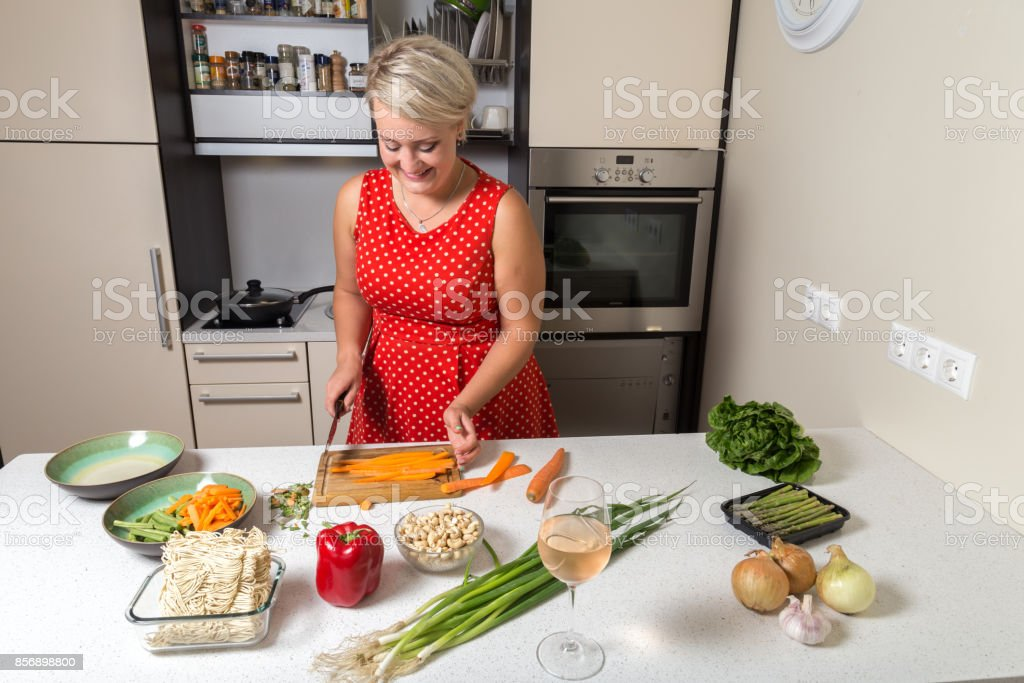 Woman chopping carrot on wooden cutting board stock photo