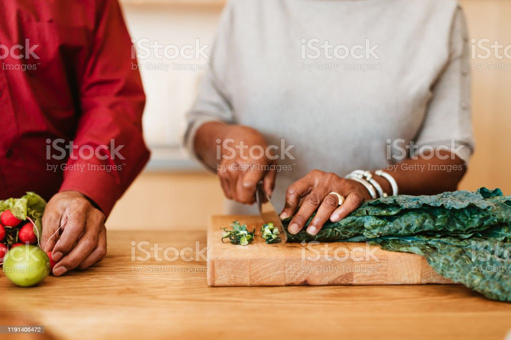 Woman chopping chard on cutting board by husband - Royalty-free Active Seniors Stock Photo