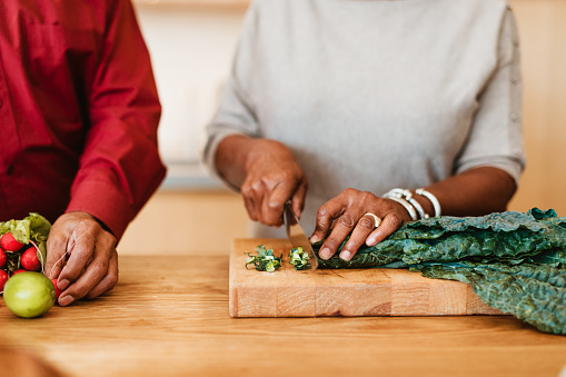 Midsection of woman chopping chard on cutting board. Female is preparing meal by husband at kitchen island. They are in kitchen together.