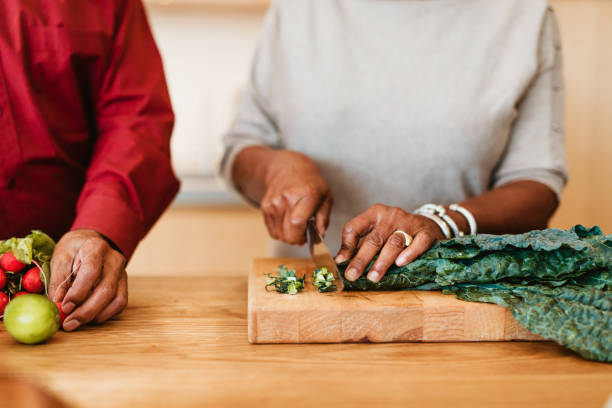 Woman chopping chard on cutting board by husband stock photo