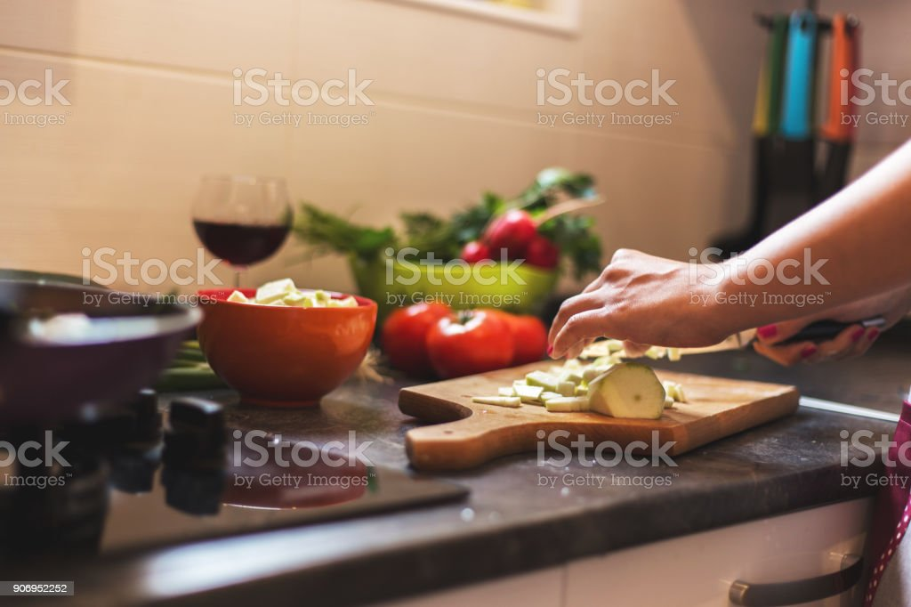 Woman chopping fresh vegetables for healthy meal stock photo