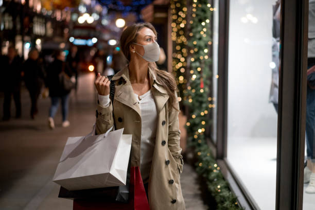 Woman Christmas shopping wearing a facemask stock photo