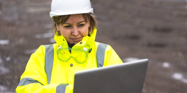 woman civil engineer close up. young woman using laptop on construction site. woman engineer developer holding laptop working Confident outdoors in construction site. Woman architect inspecting site. Civil Engineer at construction site is inspecting site. stock photo