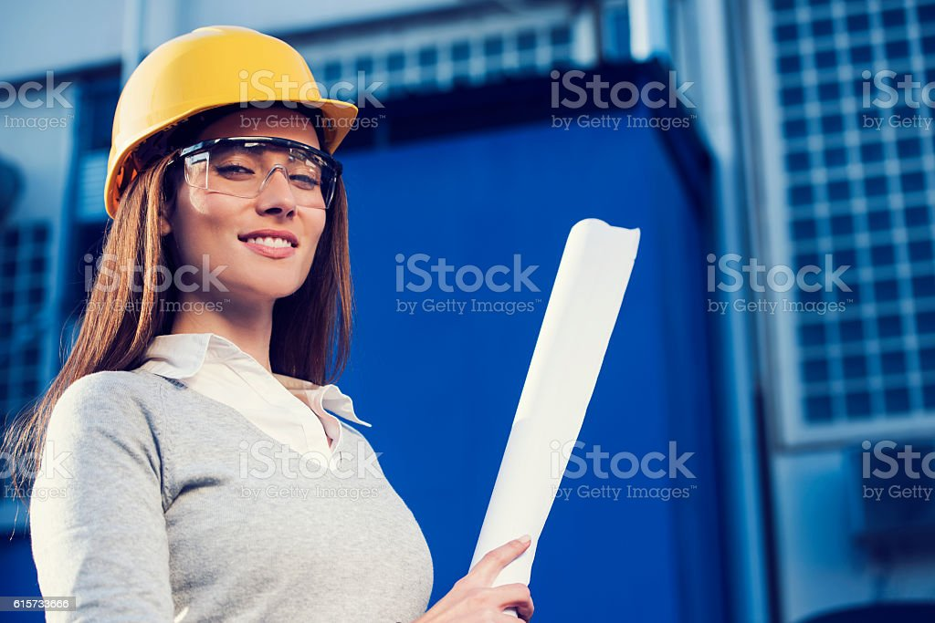beautiful woman civil engineer or architect with yellow protective...