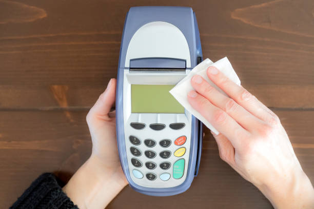 Woman cleaning a credit card reader with antibacterial white tissue or disposable wipes stock photo