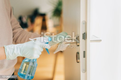 Woman in disposable gloves cleaning a door handle with a disinfection spray