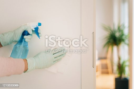 Woman in disposable gloves cleaning a light switch with a wet wipe