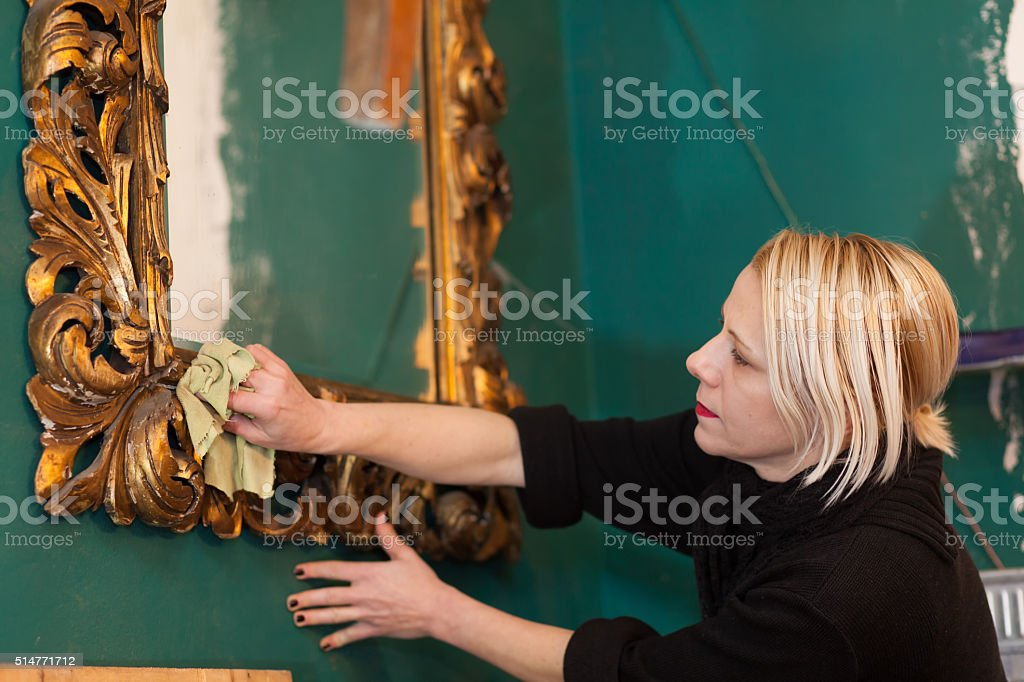 woman cleaning a mirror in preparation for auction stock photo