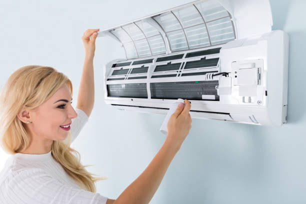 Woman Cleaning Air Conditioner stock photo
