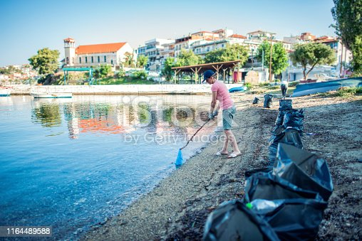 962184460 istock photo Woman cleaning beach 1164489588