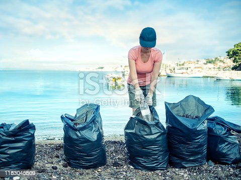 962184460 istock photo Woman cleaning beach 1183045809