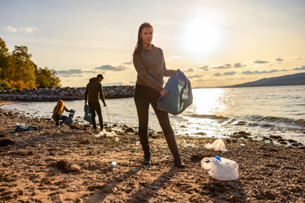 Woman cleaning beach with volunteers during sunset stock photo