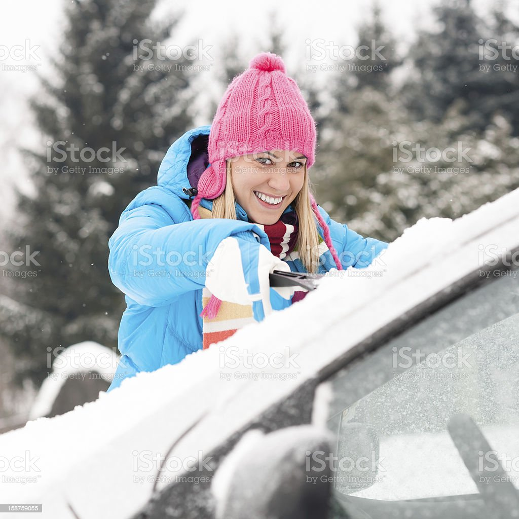 Woman cleaning car windshield of snow winter stock photo