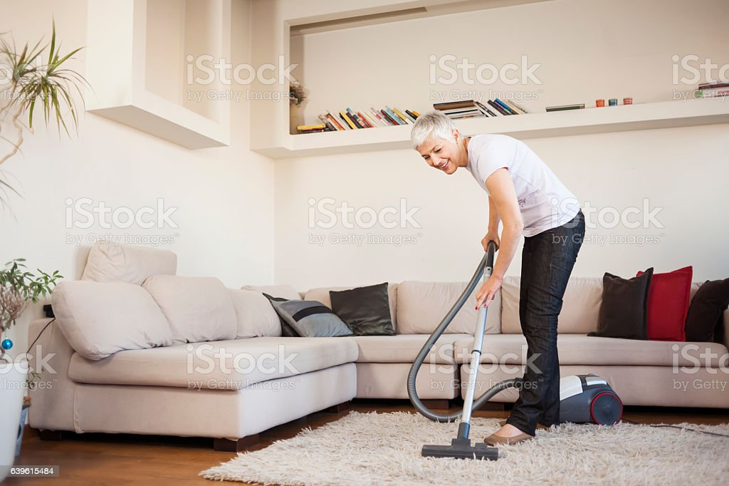 Woman cleaning carpet with a vacuum cleaner in room - foto stock