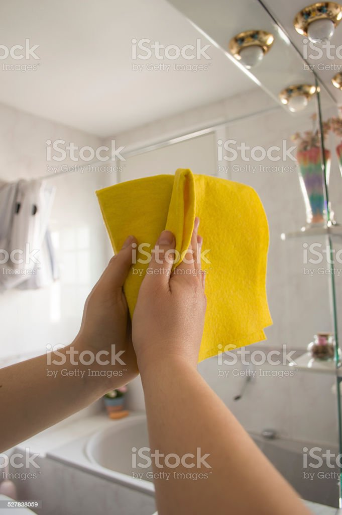 Woman cleaning cloth mirror stock photo