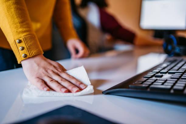 mulher limpando mesa de computador no escritório - higiene - fotografias e filmes do acervo