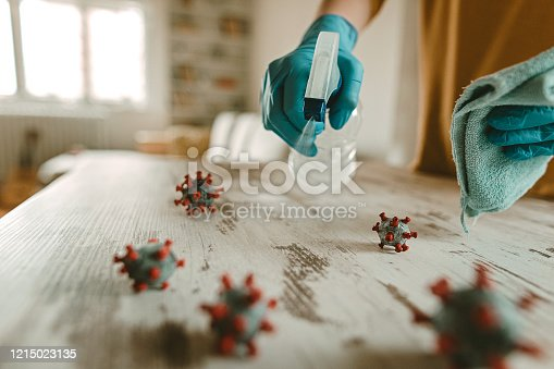 Mature woman cleaning and disinfects table in home office with a disinfectant and a rag. On the table is a model of a corona virus.