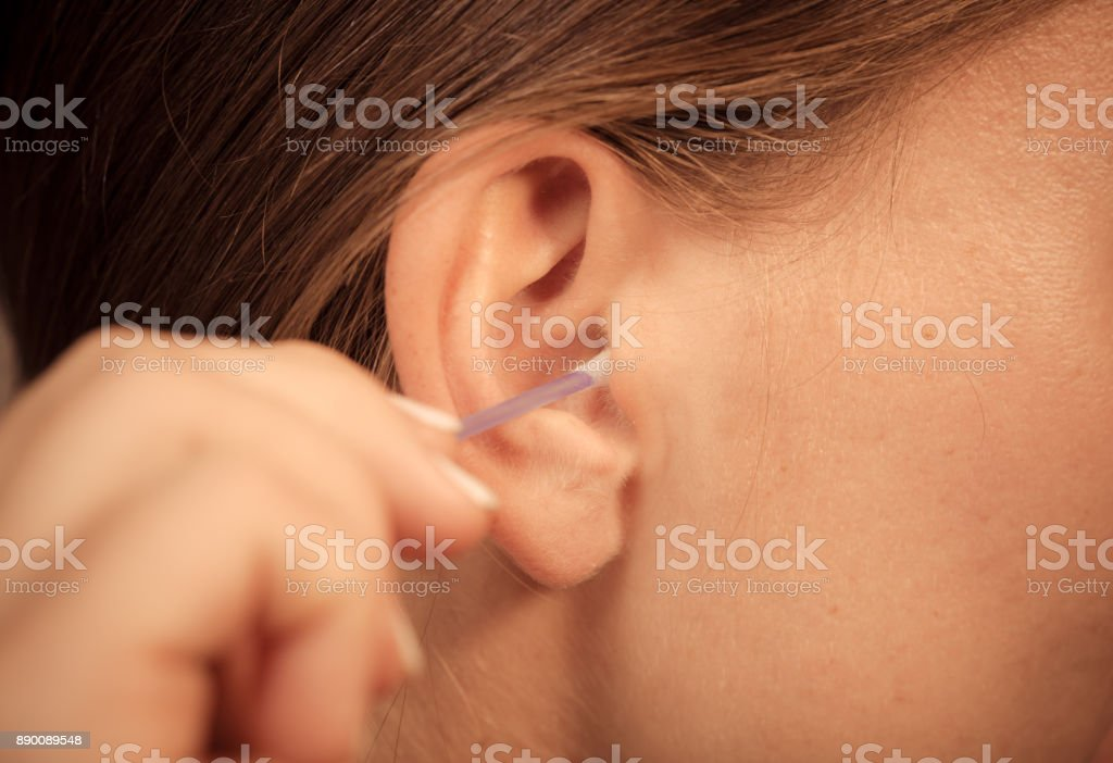 Woman cleaning ear with cotton swabs closeup stock photo