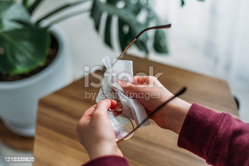 Close up of woman cleaning eyeglasses