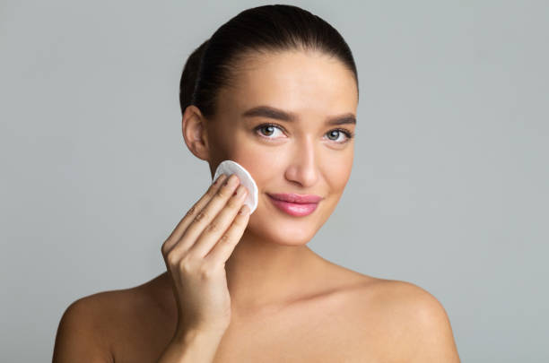 Woman Cleaning Face With Cotton Pad in Studio Woman Cleaning Face With Cotton Pad Over Grey Studio Background padding stock pictures, royalty-free photos & images
