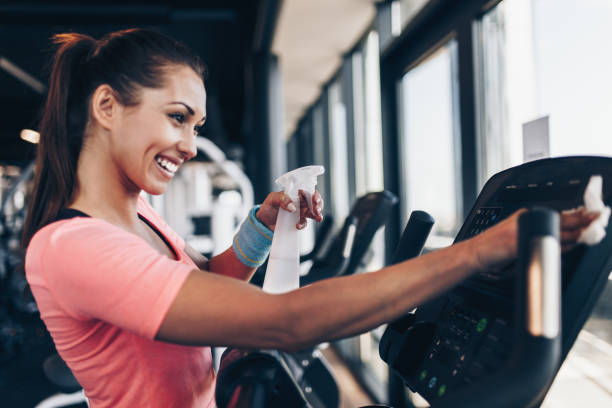 Woman cleaning fitness gym equipment Young happy and smiling woman cleaning and weeping expensive fitness gym equipment with sprayer and cloth. exercise machine stock pictures, royalty-free photos & images
