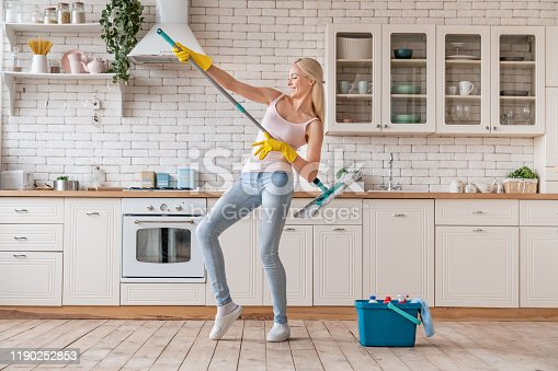 1081403344 istock photo Woman cleaning floor and playing music using mop 1190252853