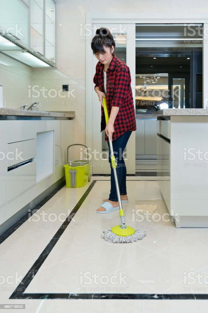 Woman cleaning floor in the kitchen.