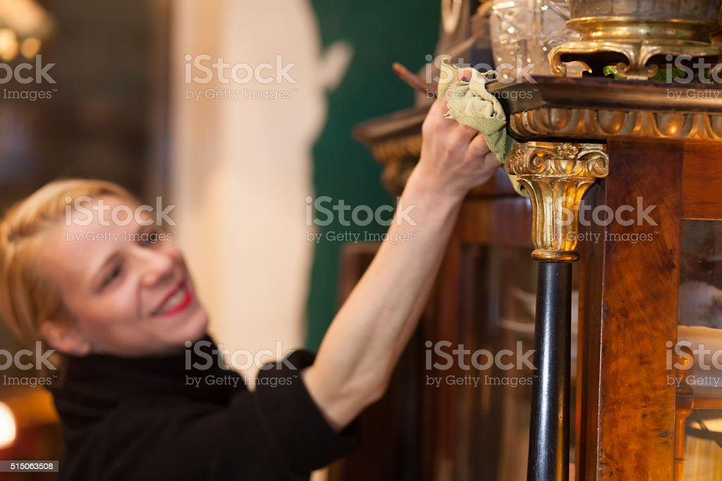 woman cleaning furniture in preparation for auction stock photo