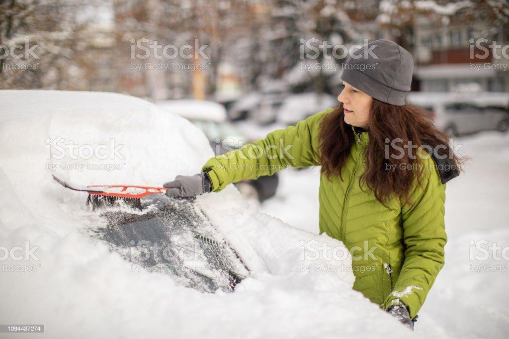 Femme, nettoyage de sa voiture de la neige - Photo de 45-49 ans libre de droits