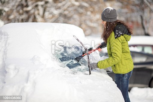Mature aged woman cleaning her car from snow on parking. She wears warm clothes and using ice scraper.