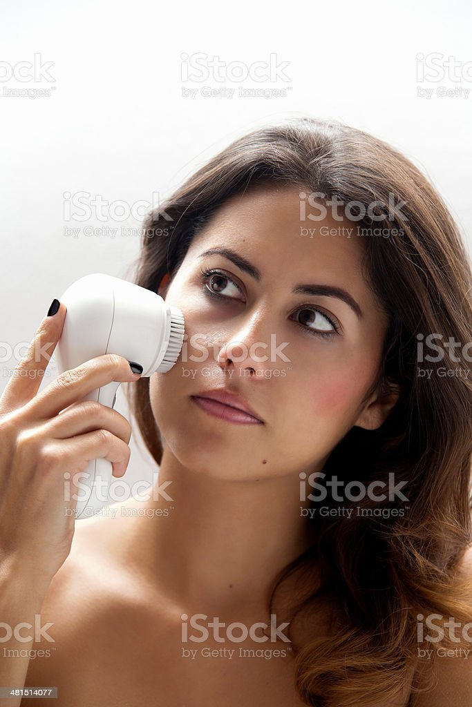 Woman Cleaning her face with brush stock photo