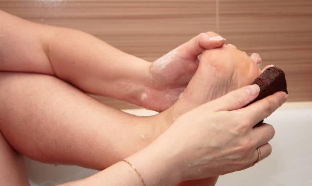 Kadın banyoda pomza ile ayaklarını temizliyor stok fotoğrafı