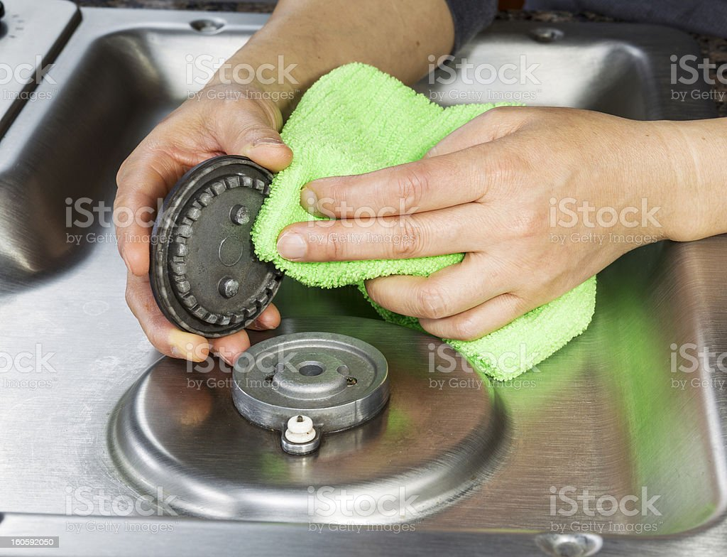 A woman cleaning her gas stove covers stock photo