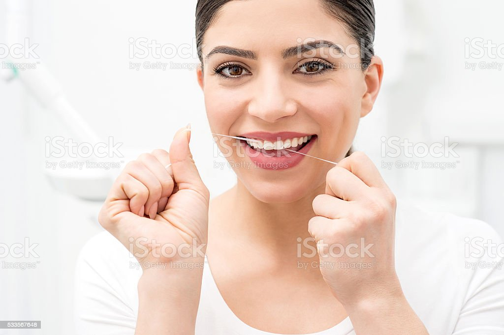 Woman cleaning her teeth by dental floss stock photo