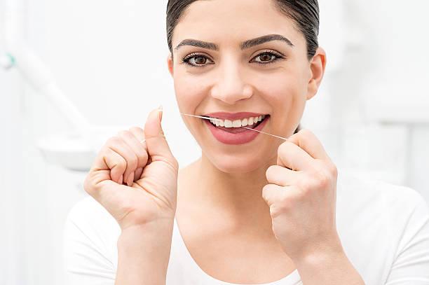 Frau Reinigung Ihrer Zähne mit Zahnseide – Foto