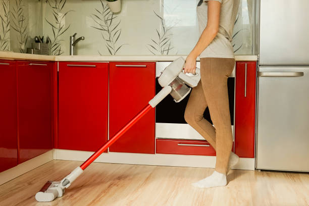 Woman cleaning house with wireless vacuum cleaner. Woman headless cleaning house with red wireless vacuum cleaner. Red kitchen, quarantine concept. cordless phone stock pictures, royalty-free photos & images