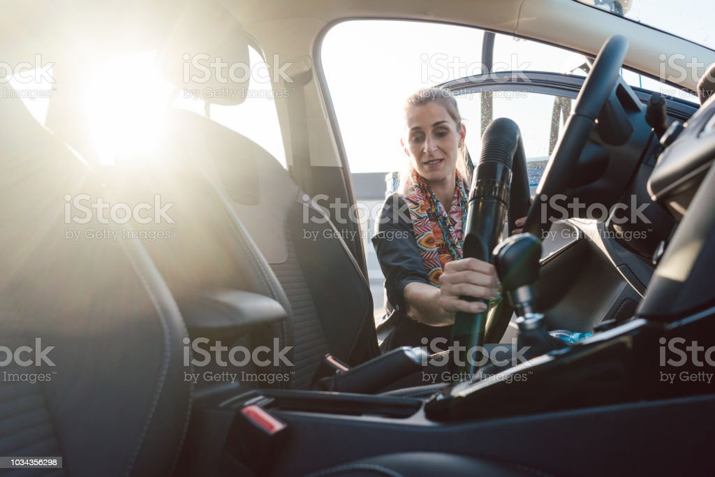 Woman cleaning inside of car with vacuum