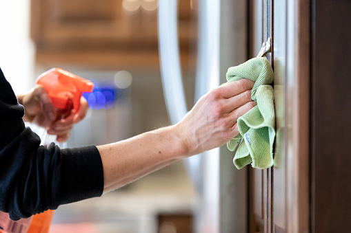 Woman Cleaning Kitchen Cabinet Handle with Disinfectant Product During Covid-19