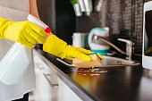 istock Woman cleaning kitchen cabinets with sponge and spray cleaner 635801162