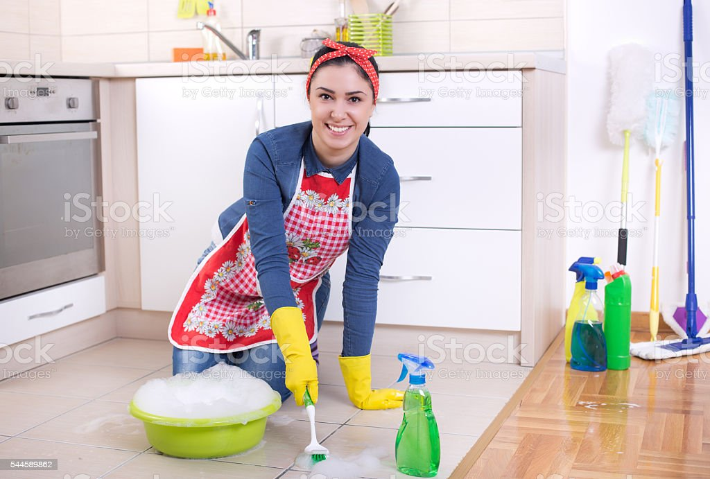 Satisfied woman scrubbing tiled floor with brush in kitchen and...