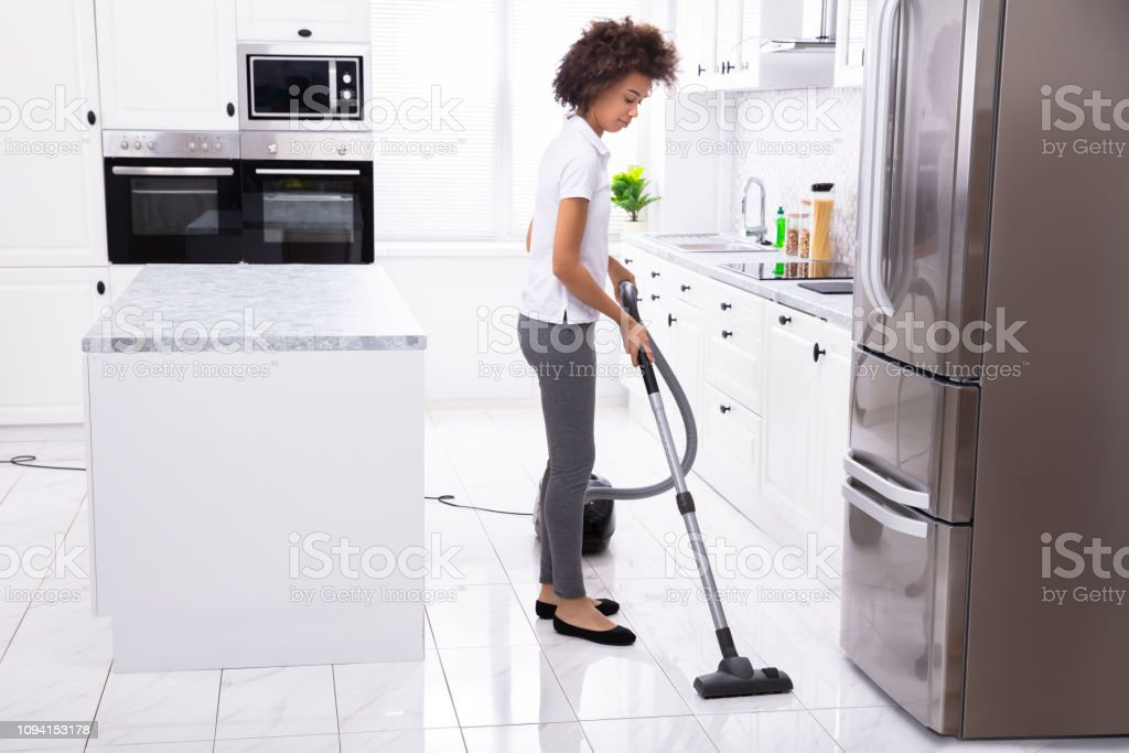 Close-up Of A Young Woman Cleaning The White Kitchen Floor With...