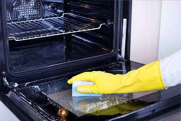 Woman cleaning oven Close up of female hand with yellow protective gloves cleaning oven door oven stock pictures, royalty-free photos & images