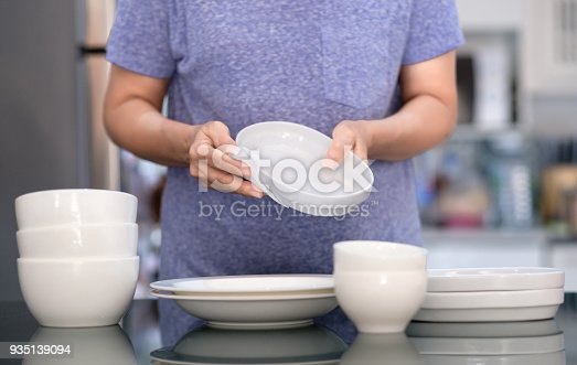 istock Woman Cleaning product concept wiping dishware cleaner in home and kitchen 935139094