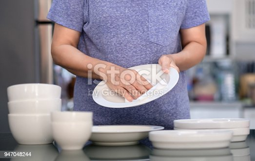 istock Woman Cleaning product concept wiping dishware cleaner in home and kitchen 947048244