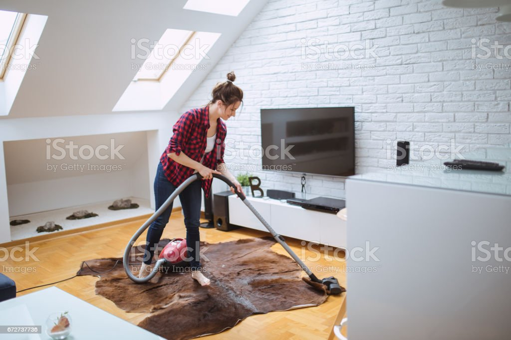 One woman, using vacuum cleaner for cleaninig her house.