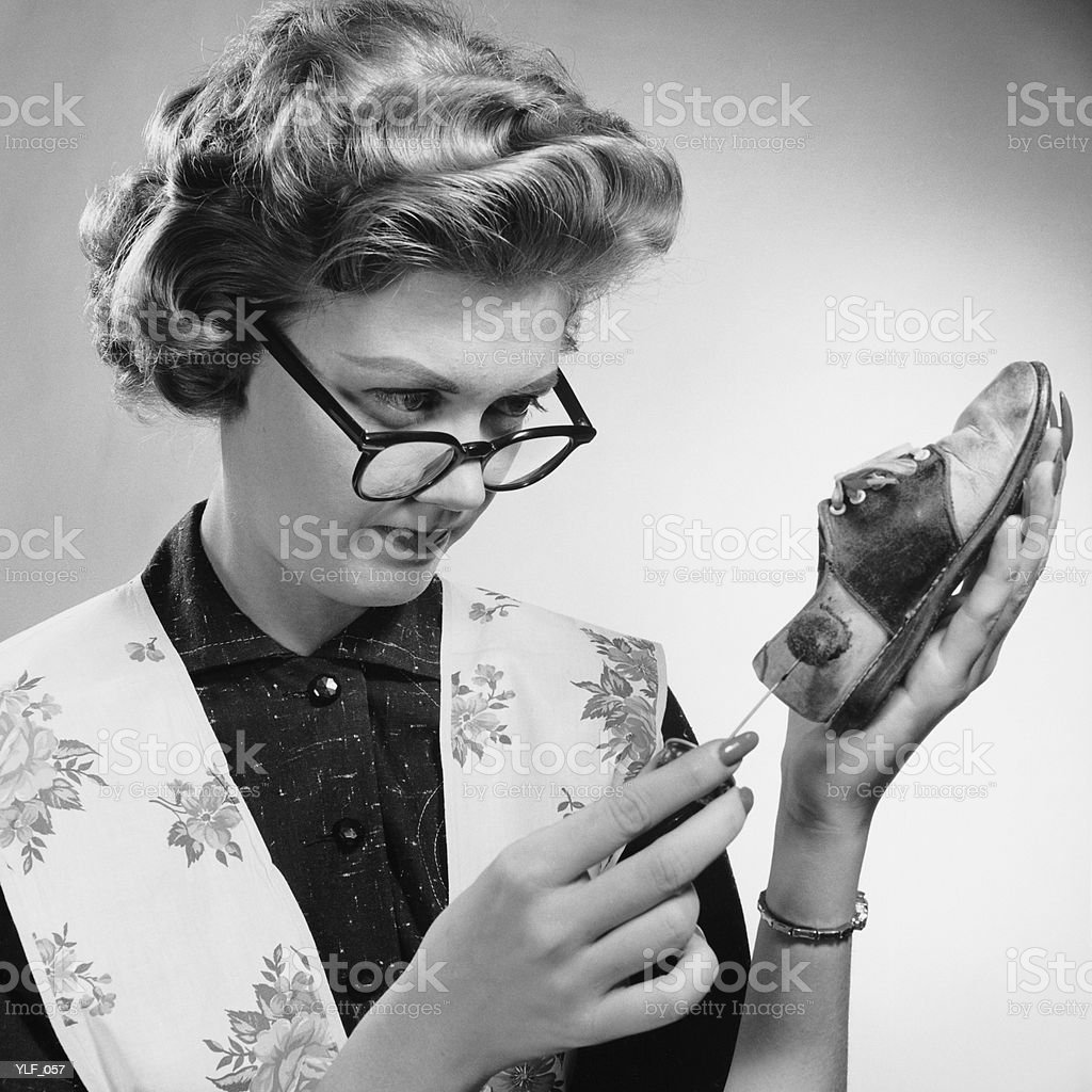 Woman cleaning scuffed shoe royalty-free stock photo