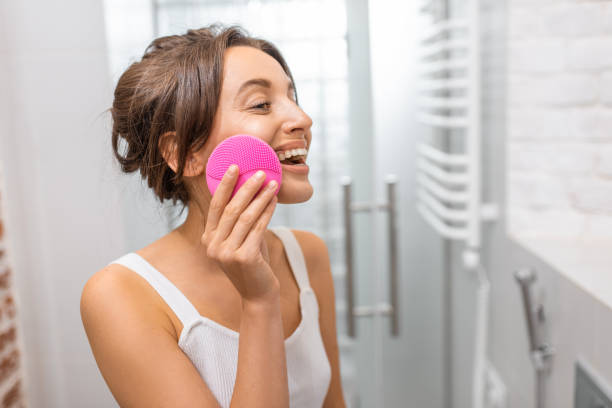 Woman cleaning skin with a special ultrasonic device stock photo
